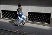 A women carries two large packs of toilet rolls into nearby offices, on 19th April, in the City of London, England.