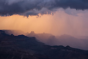 Monsoon rains are backlit by the setting sun. Grand Canyon National Park in Arizona.