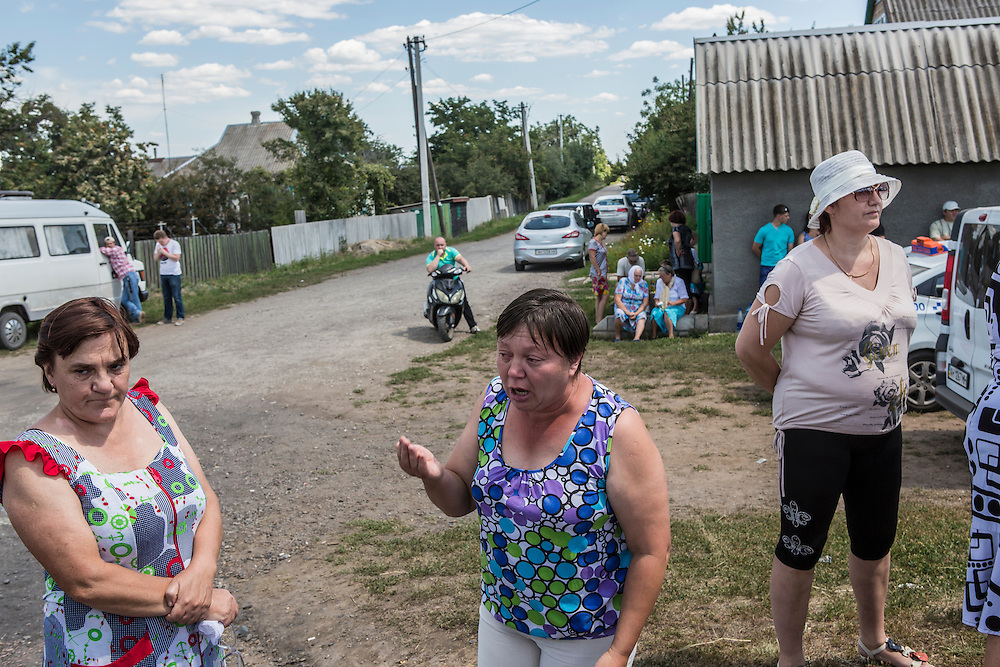 GRABOVO, UKRAINE - JULY 21: A woman becomes emotional as she talks with reporters while local residents gather to watch as the bodies of victims of Malaysia Airlines flight MH17 are removed from the scene of the crash on July 21, 2014 in Grabovo, Ukraine. Malaysia Airlines flight MH17 was travelling from Amsterdam to Kuala Lumpur when it crashed killing all 298 on board including 80 children. The aircraft was allegedly shot down by a missile and investigations continue over the perpetrators of the attack. (Photo by Brendan Hoffman/Getty Images) *** Local Caption ***