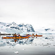 A group of kayakers navigating glassy waters and brash ice at Cuverville Island on the Antarctic Peninsula.