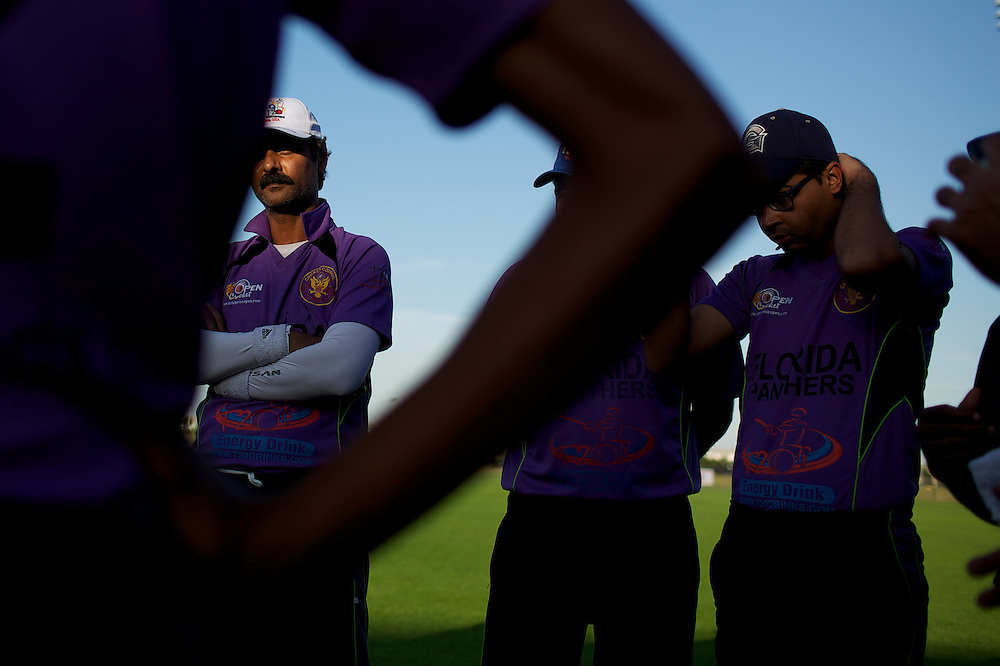 Players listen to their coach between matches at the Cricket US Open in Lauderhill, Florida.
