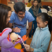 Tufts Schweitzer fellow students help teach local kids about dental hygiene at Chinatown's annual Oak Street Fair organized by Boston Chinatown Neighborhood Center at Josiah Quincy Elementary School. (Zara Tzanev for Tufts University)