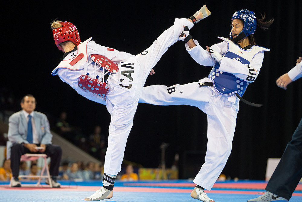 Saul Gutierrez (R) of Mexico trades kicks with Maxine Potvin of Canada during their gold medal contest in the men's Taekwondo -68kg division of at the 2015 Pan American Games in Toronto, Canada, July 20,  2015.  AFP PHOTO/GEOFF ROBINS