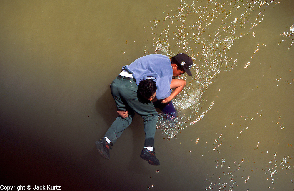 """EL PASO, TEXAS, USA: A """"coyote"""" or guide, carries an undocumented immigrant from Ciudad Juarez, Chihuahua, Mexico, across the Rio Grande River to El Paso, Texas.  PHOTO © JACK KURTZ  BORDER   IMMIGRANTS  WATER  TRAFFICKING"""