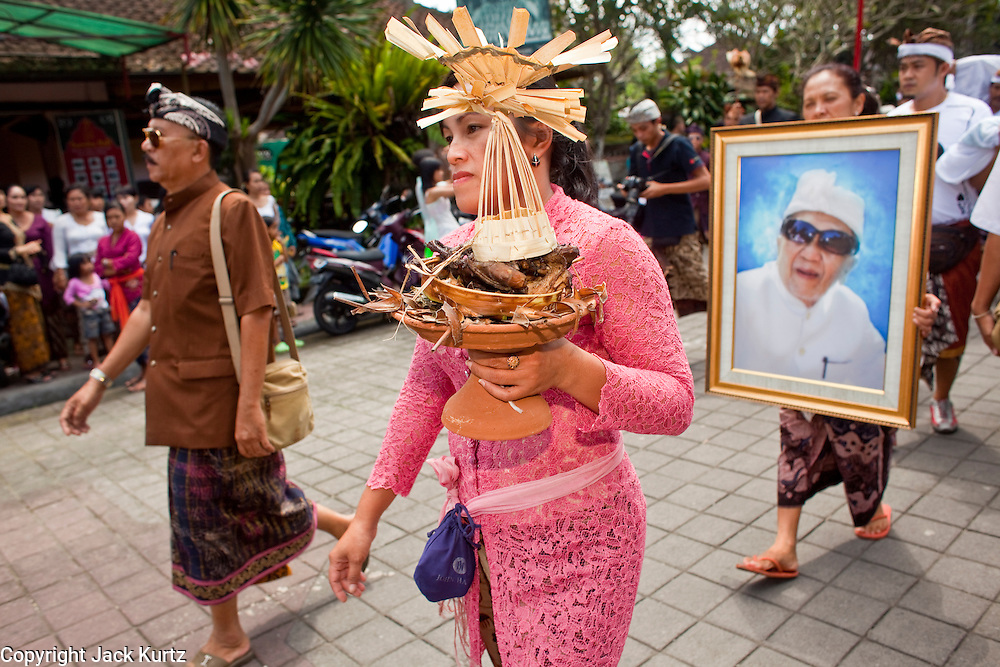 Apr. 25 -- UBUD, BALI, INDONESIA:   The funeral procession for Cokorde Gede Raka, a member of Ubud's royal family Sunday, Apr. 25. Balinese are Hindus and cremate their dead. Balinese funerals are elaborate - and expensive - affairs. A funeral for one person costs a minimum of 45 million rupiah (about $5,000 US). The body is placed into the bull's body at the cremation and cremated in the bull. The funeral pyre is burnt adjacent to the bull. That is what a family may earn in two to three years. The result is that only the rich can afford formal cremations. The body (in the casket) is placed in the top of the funeral pyre and the procession takes the body to the cremation site. The funeral pyre, and the body, are spun at intersections to confuse the spirits so the soul doesn't try to return to its home and to confuse evil spirits.    PHOTO BY JACK KURTZ
