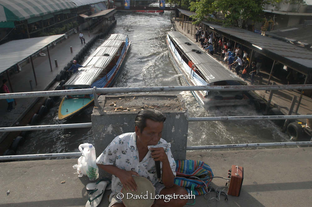 A blind beggar waits for tourist near one of Bangkok's many canals.