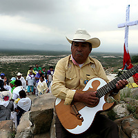 A mariachi strums his guitar as a healer and follower of Nino Fidencio, a curandero or healer who passed away in the 1938, squeezes lime in the eye of a follower as part of a healing just outside of Espinazo, Mexico on Thursday, October 19, 2006. Followers of Nino Fidencio believe that his spirit can posses other healers, who once possessed, speak in child-like voices and perform a variety of medical cures on their followers. His believers, an estimated 20,000, gather in his hometown for a three-day festival twice a year in March and October. (Photo/Scott Dalton)