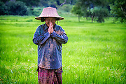 Lut, a rice field worker, says goodbye as she heads for home after a day of planting rice in Nakhon Nayok Thailand Aug 16, 2016. PHOTO BY LEE CRAKER