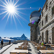 Gornergrat Kulm Hotel & restaurant was built from 1897-1907 at 3120 meters elevation, reached from Zermatt via the Gornergrat railway, in the Pennine/Valais Alps, Switzerland, Europe. The two tower domes were added in 1996 to enclose the KOSMA telescope and Gornergrat Infrared Telescope. The Gornergrat rack railway (GGB) takes you to a spectacular ridge (at 3135 m or 10,285 ft) between Gornergletscher and Findelgletscher, with views of more than twenty 4000-meter-high peaks, the highest being Dufourspitze (Monte Rosa massif), Liskamm, Matterhorn, Dom and Weisshorn. Gornergrat train, opened in 1898, climbs almost 1500 m or 4900 ft via Riffelalp and Riffelberg. This image was stitched from multiple overlapping photos.