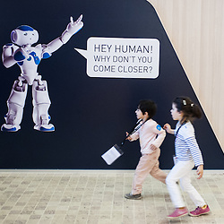 Lyon, France - 19 March 2014: two children run past a banner of NAO Robot at Innorobo 2014, the 4th international trade show on service robotics.