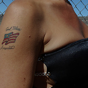 Ricki waits for customers at the Salt Wells Ranch bordello in the middle of the Nevada desert. She had this patriotic tattoo done after September 11.