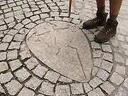 Leaving Palas de Rei on the Camino de Santiago there was the cross and symbol of Saint James sunk into the walkway. One pilgrim stops to admire the paving stones.