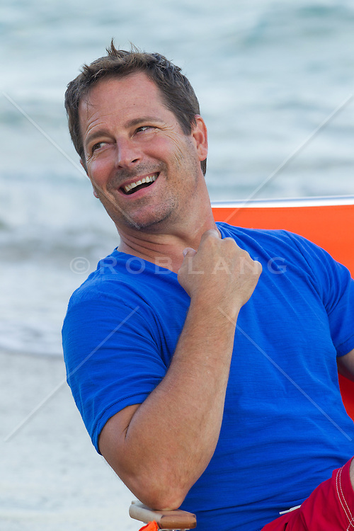 good looking middle aged man laughing while sitting in a beach chair by the ocean