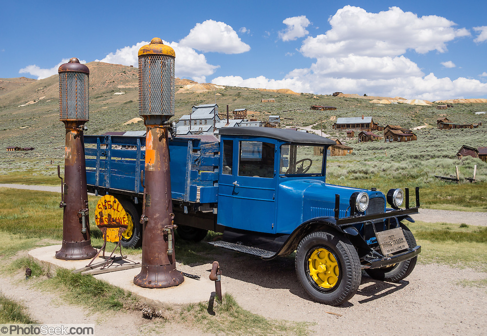 "1927 Dodge Graham blue truck at antique gas station in Bodie, California's official state gold rush ghost town. Bodie State Historic Park lies in the Bodie Hills east of the Sierra Nevada mountain range in Mono County, near Bridgeport, California, USA. After W. S. Bodey's original gold discovery in 1859, profitable gold ore discoveries in 1876 and 1878 transformed ""Bodie"" from an isolated mining camp to a Wild West boomtown. By 1879, Bodie had a population of 5000-7000 people with 2000 buildings. At its peak, 65 saloons lined Main Street, which was a mile long. Bodie declined rapidly 1912-1917 and the last mine closed in 1942. Bodie became a National Historic Landmark in 1961 and Bodie State Historic Park in 1962."
