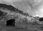 """17 December 2008. Roossenekal, Mpumalanga. During the """"Mapoch's War"""" of 1883, the ZAR troops based in tht town of Roossenekal, got a hold of a substantial amount of dynamite. To break the siege, they decided to dig a tunnel from town to """"Spitskop"""" in order to place the dynamite in the centre of the small hill, to blow it up. They hit granite pretty quickly and needless to say, the effort failed. Storm clouds build over the hill where Ndebele warriors kept watch over the town below. Today there are still old graves to be found. Leonie Marinovich"""