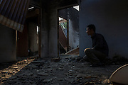 Kanti J. Rengma kneels in the burnt remains of his aunt's home in Chokihola Block, Karbi Anlong. Within 2 miles of her home there is both a Central Reserve Police Force base and a Assam state police station. Both groups failed to protect the Rengma public and prevent 22 of their homes from being burned. Image © Jonah Markowitz/Falcon Photo Agency