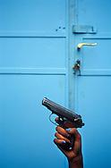 An off-duty Eritrean female soldier's hand with blue nail varnish, holding a handgun, Asmara, Eritrea.