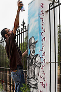 Celebrated young pakistani artist Asim Butt on a journey of political graffiti through Pakistan during the summer of 2009..Asim works on the piece 'Room for Two' at Jinnah's tomb in karachi