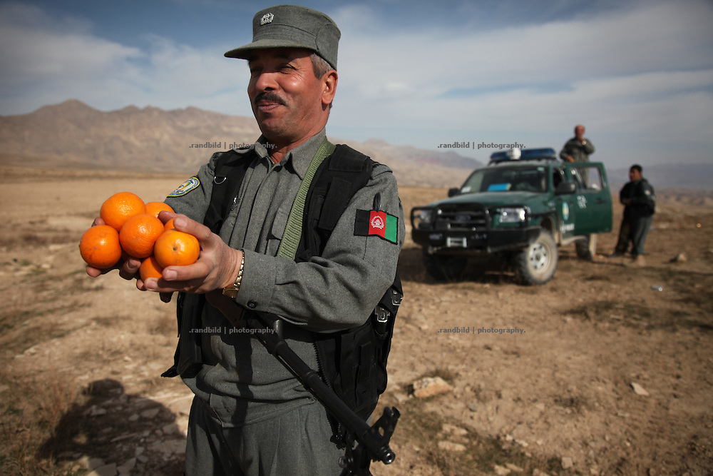 A police officer of the Afghan National Police (ANA) offers organges.