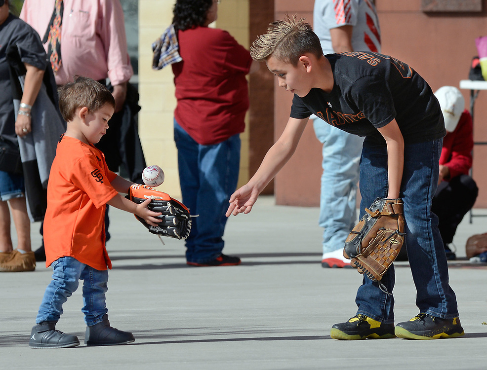 jt040617d/sports/jim thompson/  Dion Luna -9  of Santa Fe plays catch with his little brother Gabriel Luna-2 as they with for the gates to open for the season opener for the Albuquerque Isotopes.  April 06, 2017. (Jim Thompson/Albuquerque Journal)