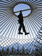 Man applying weight to set the frame of yurt into place. Alaska.