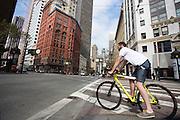 Een man op een gele fietst wacht in San Francisco. De Amerikaanse stad San Francisco aan de westkust is een van de grootste steden in Amerika en kenmerkt zich door de steile heuvels in de stad. Ondanks de heuvels wordt er steeds meer gefietst in de stad. <br /> <br /> Cyclists in San Francisco. The US city of San Francisco on the west coast is one of the largest cities in America and is characterized by the steep hills in the city. Despite the hills more and more people cycle