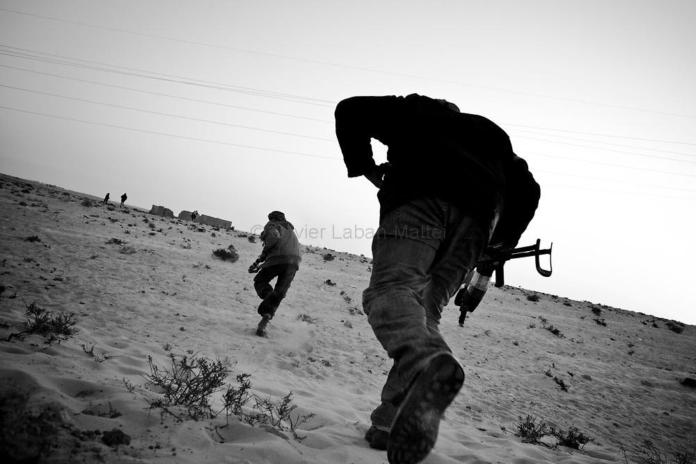 Des combattants rebelles courent pour éviter les balles tirées par l'armée loyaliste, le 25 mars 2011 à une dizaine de kilomètres de la ville d'Aj Dabiya.