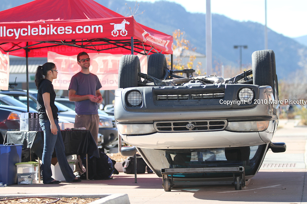 SHOT 11/6/10 1:29:04 PM - Members of Driven to Drive Less display a car turned upside down and offer free bike tunes and maintenance in front of the Whole Foods grocery store in Boulder, Co. on Saturday November 7, 2010. Driven to Drive Less is a program being undertaken by the city of Boulder, Co. that encourages participants to stimulate long term travel behavior change and to creatively demonstrate to the general public the ability of Boulder residents to live car free or car lite. Participants receive benefits and discounts at local stores for pledging to give up driving their vehicle one day a week. (Photo by Marc Piscotty / © 2010)