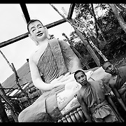 Buddhist monks look on at a pagoda near the Cambodian border with Thailand.  Once a stronghold for the Khmer Rouge residents in the area now seek employment as farmers and laborers.