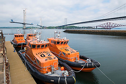 View of three bridges crossing the River Forth and modern lifeboats at South Queensferry in Scotland United Kingdom.