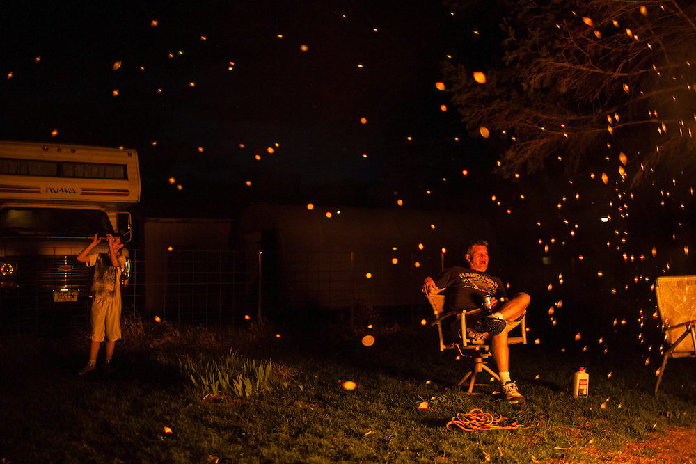 Joe McFarland, left, takes a picture as Steve McFarland watches a bonfire burn in his back yard on Sunday, March 25, 2012 in Webster City, IA.