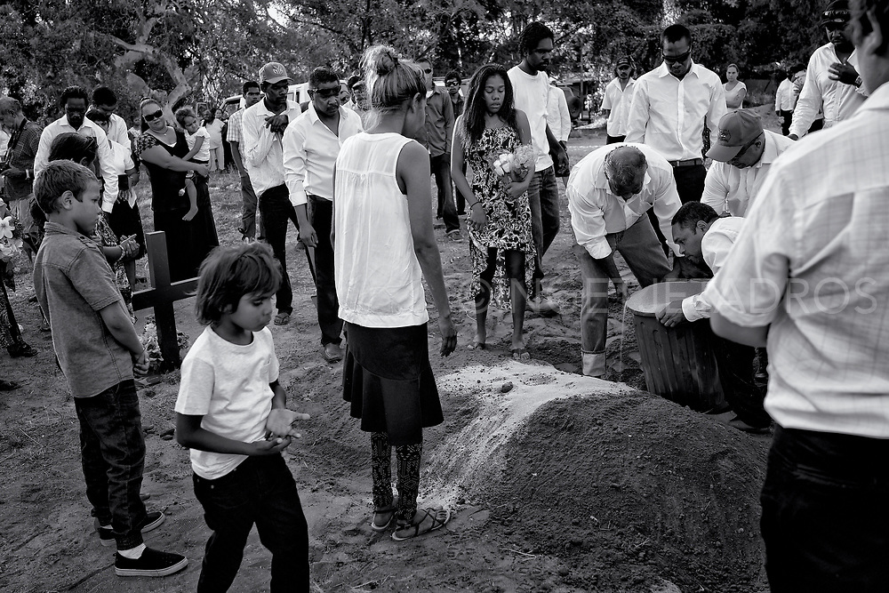 Family members pouring sand on the grave of of their beloved in the Djarindjin community which is an Aboriginal community located 170 km north of Broome. Western Australia