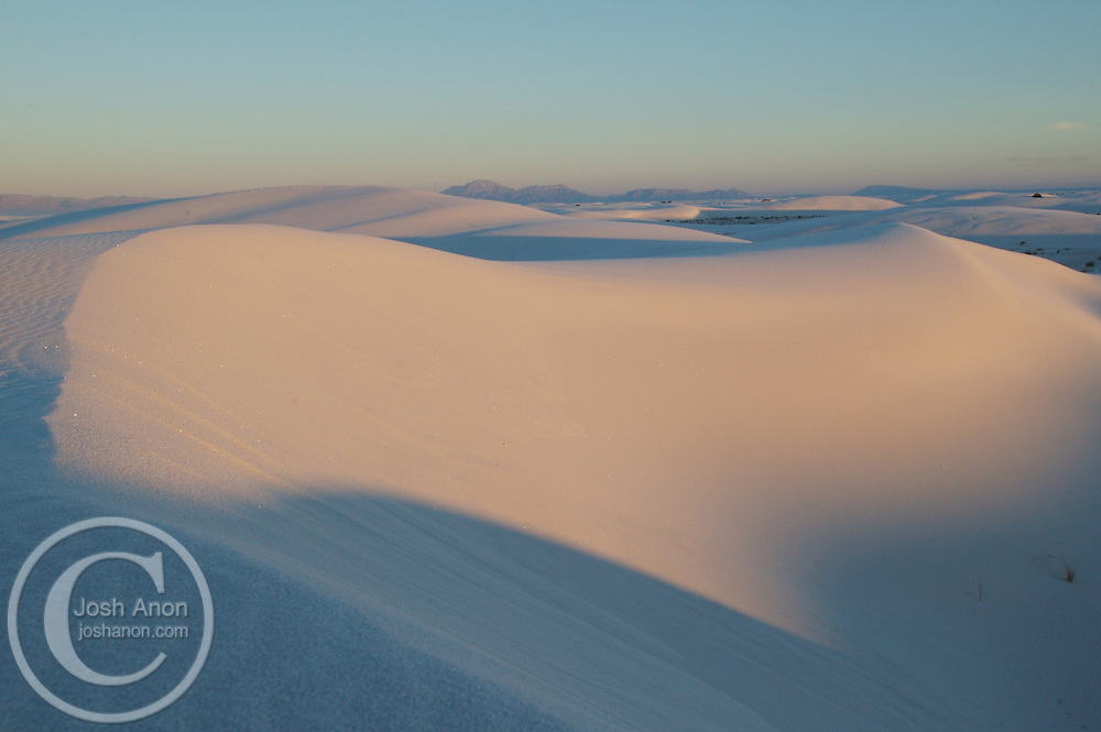 A dune glistens colorfully beneath the sunrise at White Sands National Monument, New Mexico.
