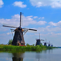 Five Windmills in Kinderdijk, Netherlands<br /> Children Dike is the Dutch translation for Kinderdijk, Netherlands, where 19 polder windmills were built beginning in 1740.  It is also the site of the &ldquo;Cat and the Cradle&rdquo; legend when a cat saved a baby from drowning during a 1421 flood. Today, the function of these picturesque relics has been replaced by 2,000 wind turbines scattered across Holland.