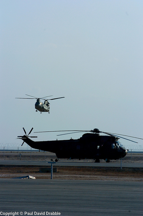 A Chinook helicopter takes off in the background as a Sea king Helicopter sits on the tarmac at Basra Air Station Iraq March 2005