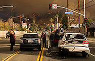 Motorists exchange information after a car accident as a wildfire burns in the hills just north of the San Gabriel Valley community of Glendora, Calif. on Thursday, Jan 16, 2014. Southern California authorities have ordered the evacuation of homes at the edge of a fast-moving wildfire burning in the dangerously dry foothills of the San Gabriel Mountains. (AP Photo/Ringo H.W. Chiu)