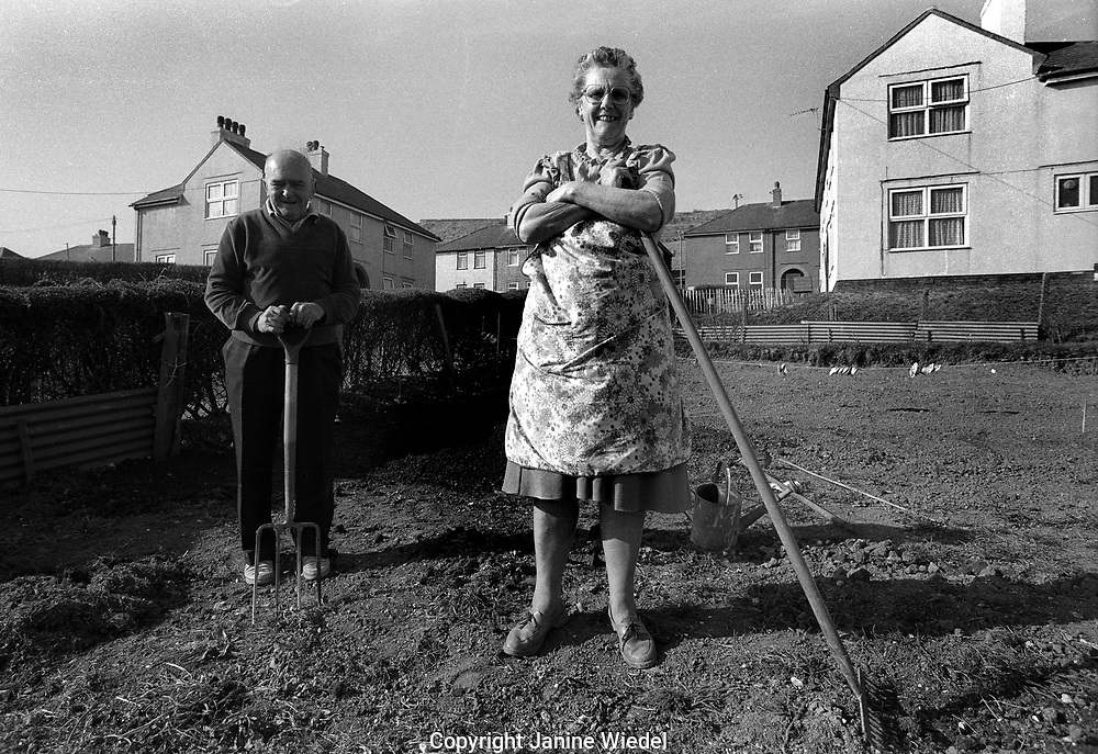 Couple tending their plot of land behind the house preparing to grow vegetable garden in town of Dover in Kent