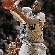 SHOT 2/26/11 5:12:27 PM - Colorado's Alec Burks (#10) grabs a rebound over Texas' Cory Joseph during their regular season Big 12 basketball game at the Coors Events Center in Boulder, Co. Colorado upset the fifth ranked Texas 91-89. Burks scored 33 points in the win. (Photo by Marc Piscotty / © 2011)