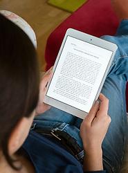 Woman reading Kindle ebook on an iPad mini tablet computer