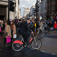 A businessman wearing a helmet for safety tries to cross Oxford circus at rush hour on a Boris bike - called after London mayor Boris Johnson who introduced the scheme to London.