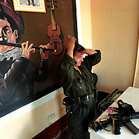 A FARC rebel  fixes her hair in San Vicente, about 180 miles southwest of Bogota. San Vicente was the principle town in the former rebels safe haven where the government had pulled out all troops and police and left it to be ruled by the FARC rebels. The safe haven was a concession to the rebels to help get peace talks started. After three years of failed peace talks the government, frustrated by the rebels unwillingness to find a peaceful solution, and the fact that the rebels were using the safe haven to deal drugs and hide kidnapping victims, sent troops into the region to reclaim it. (Photo/Scott Dalton)