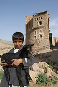 Boy with young goat. Bait Baus. A near abandoned village just outside San'a'. Built on the ridge of a hill. One side looks down into the valley with Sanaa in the distance. It is a stunning collection of old houses, a mosque, great views, good architectural details.