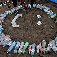 Smiley face made from empty bottles and other rubbish at 'collection point' number 1 near Röszke where refugees were required by the Hungarian police to board buses and be taken for registration. This site is a kilometre in from a gap in the border fence along an old railway line, one of the principal access routes used by refugees entering Hungary from Serbia.   Food and basic supplies were available here thanks to donations and volunteers, with support from UNHCR. Thousands of refugees crossed the border into Hungary heading towards Western Europe, until a 15 September deadline set by the Hungarian authorities to seal its border fence and bring in new restrictive laws limiting access of refugees to its territory, effectively stopping the flow of refugees.