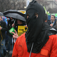 A protester dressed in a black hood and mock prison garb demonstrates on the Ellipse in Washington, D.C. against the U.S. war in Iraq.