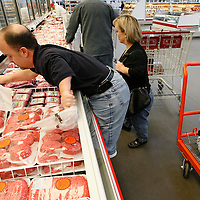 Chris Kotzian (L) climbs up to reach a bag on a shopping trip with wife Barb (C) and son Adam (R) in Thornton, Colorado March 25, 2010.  Chris, Barb and Adam are achondroplasia dwarfs with a rare genetic disorder of bone growth.  Preferring to be called little persons Chris and Barb are active in the Little People of America, the only dwarfism support organization that includes all 200+ forms of dwarfism.  REUTERS/Rick Wilking (UNITED STATES)
