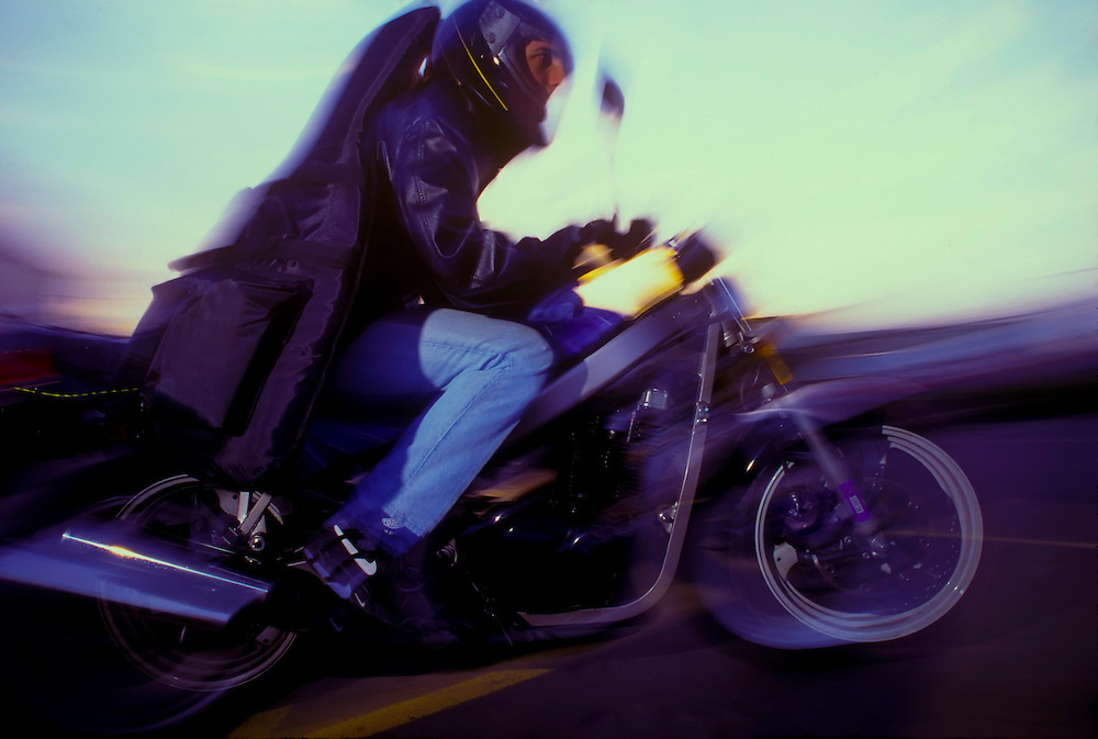 Musician wearing light blue jeans and a helmut with a guitar in a black case on his back speeding down the highway in a blur at dusk in Philadelphia, PA.