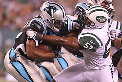 Aug 26, 2012; East Rutherford, NJ, USA; Carolina Panthers running back Jonathan Stewart (28) is tackled by New York Jets linebacker Bart Scott (57) during the first half at MetLife Stadium.