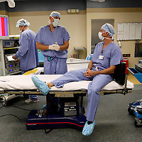 Bariatric surgeon Dr. Michael Snyder (R) assisted by surgical assistant Anthony Cavello (C) rests on the surgical table as he waits to perform a laparoscopic gastric bypass at Rose Medical Center in Denver August 30, 2010.  Snyder does four types of bariatric procedures completing 451 just last year. REUTERS/Rick Wilking (UNITED STATES)