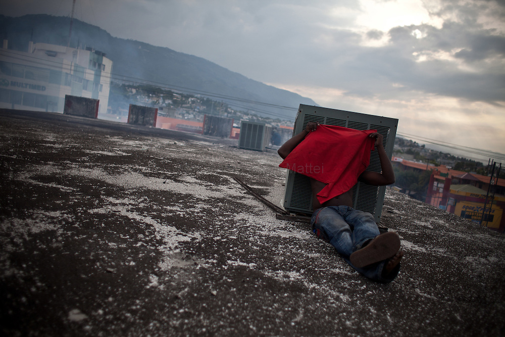 Martelly's supporters demonstrate, in the streets of Port-au-Prince, to protest against the results of the presidential elections and the defeat of their leader, Michel Martelly. /// A Martelly's supporter hides his face on a roof of Port-au-Prince, to avoid Minustah's tear gas.