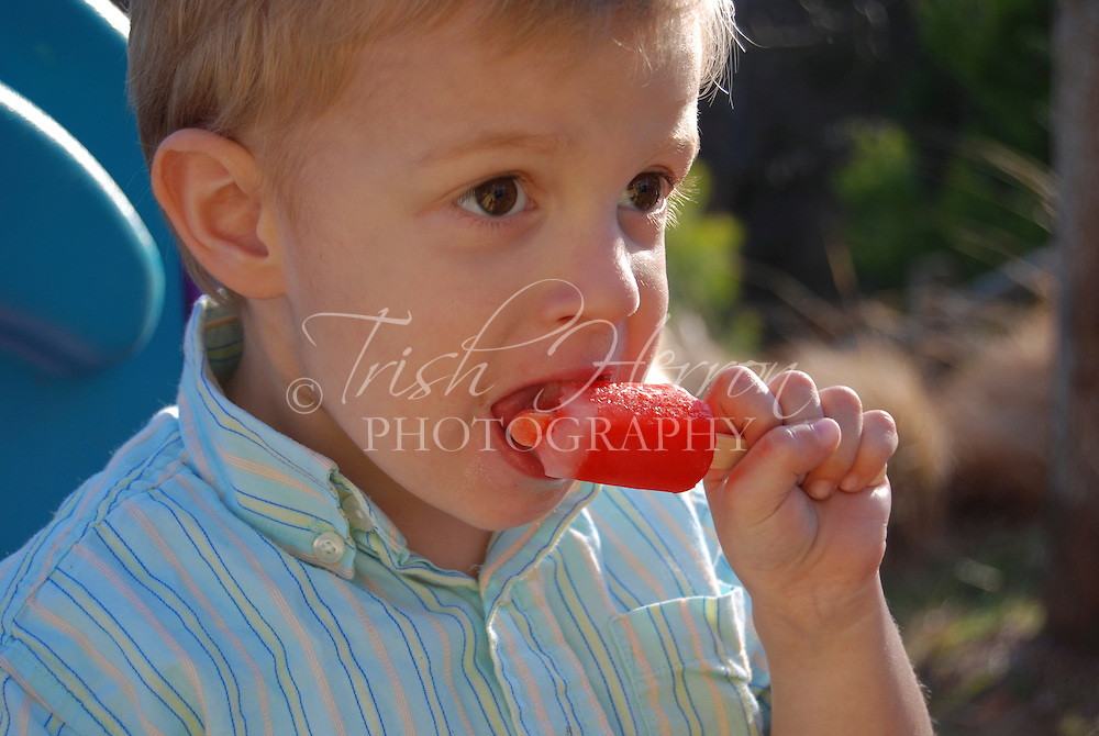 A small boy enjoys a red popsicle outdoors on a sunny afternoon.